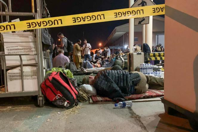 Des ressortissants français et leurs collègues afghans attendent de monter à bord d'un avion de transport militaire français à l'aéroport de Kaboul le 17 août 2021 pour être évacués d'Afghanistan après la prise de contrôle militaire du pays par les talibans.