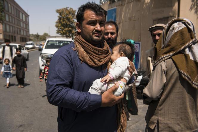 Le photographe de l'Agence France-Presse Noorullah Shirzada porte son bébé à l'intérieur de la zone verte de Kaboul pour être évacué, le 16 août 2021.