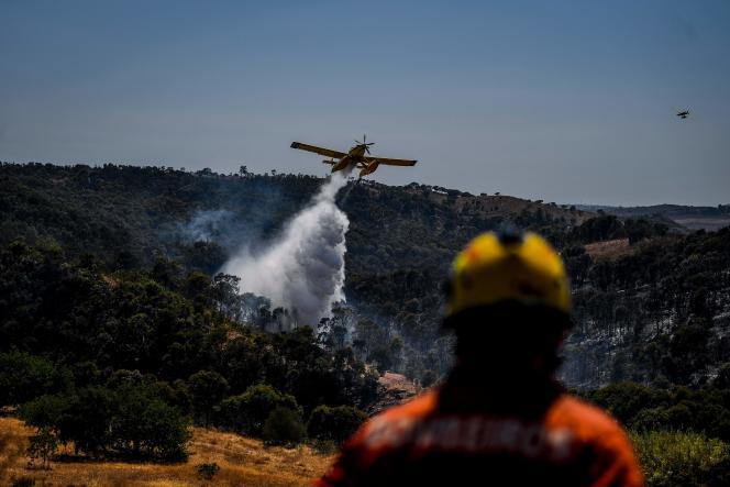 Para ajudan berusaha memadamkan api di dekat Tavira, di selatan Portugal, pada 17 Agustus.