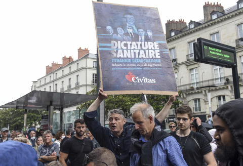 """A member of fundamentalist Catholic organisation Civitas holds a placard reading """"health dictatorship"""" during a demonstration against the compulsory vaccination for certain workers and the mandatory use of the health pass called by the French government, in Nantes, western France on July 24, 2021. - Since July 21, people wanting to go to in most public spaces in France have to show a proof of Covid-19 vaccination or a negative test, as the country braces for a feared spike in cases from the highly transmissible Covid-19 Delta variant. (Photo by Sebastien SALOM-GOMIS / AFP)"""