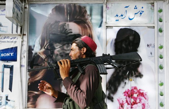 Seorang pejuang Taliban di depan salon kecantikan di mana wajah wanitanya ditutupi cat, di Kabul, Rabu, 18 Agustus 2021.