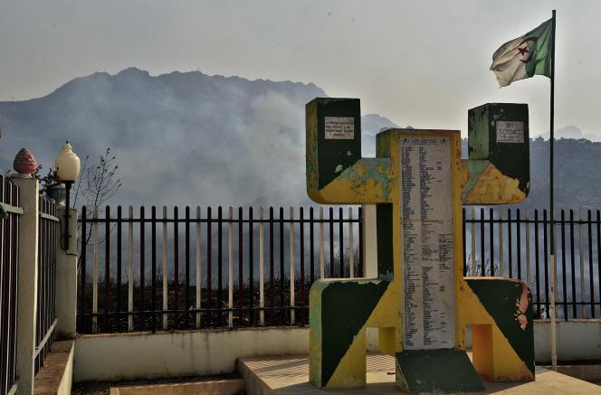 De la fumée s'échappe des feux de forêt face au monument des martyrs de la commune de Yatafen, en Algérie, le 13août 2021.