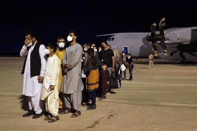 Un groupe de ressortissants afghans arrivés de Kabouldans un Airbus de l'armée de l'air espagnole patientent sur la base aérienne de Torrejon de Ardoz, près de Madrid, le 19 août.Belen Diaz/AFP