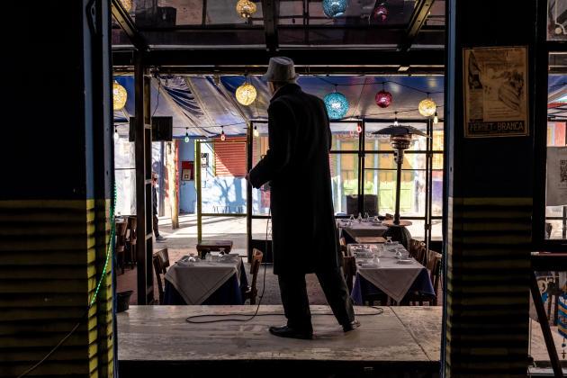 Un chanteur de tango devant la salle vide du restaurant « La vieille Rôtisserie» dans le quartier de La Boca, à Buenos Aires, en Argentine le 12 aout 2021.