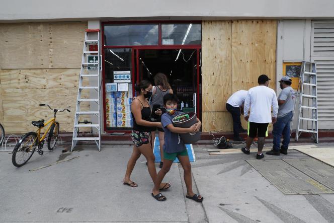 En Tulum, los mexicanos se preparan para la llegada del huracán Grace y aseguran una tienda el 18 de agosto de 2021.