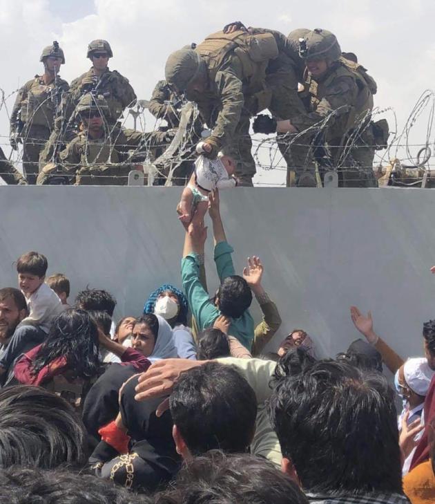 Un soldat américain prend en charge un enfant tendu par sa famille, à l'aéroport de Kaboul, vendredi 20août.