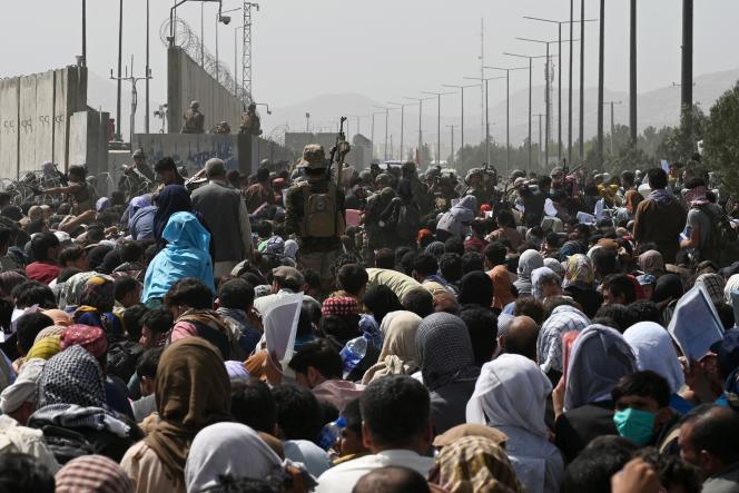 Des milliers d'Afghans attendent aux abords de l'aéroport de Kaboul dans l'espoir de fuir leur pays, le 20 août 2021.