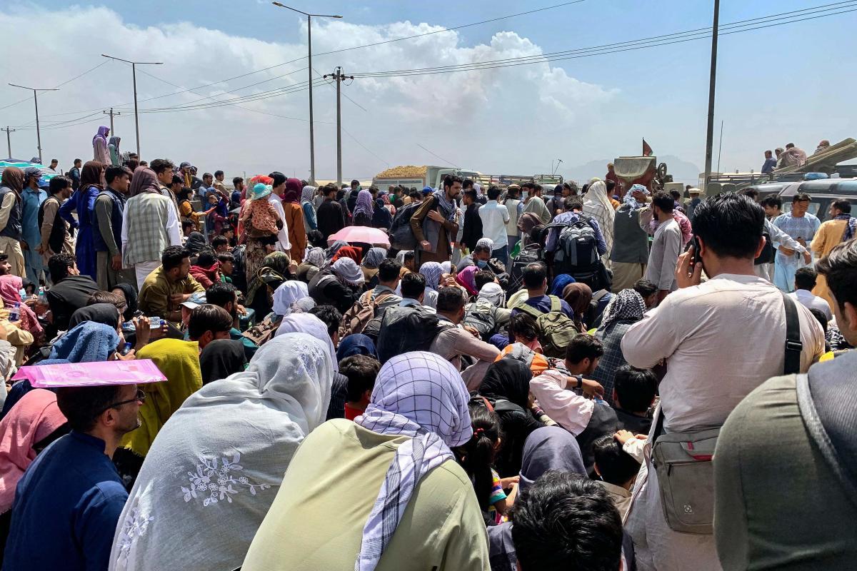 Des familles afghanes attendent d'embarquer dans un avion de l'armée américaine depuisle secteur militaire de l'aéroport de Kaboul, vendredi 20 août 2021.