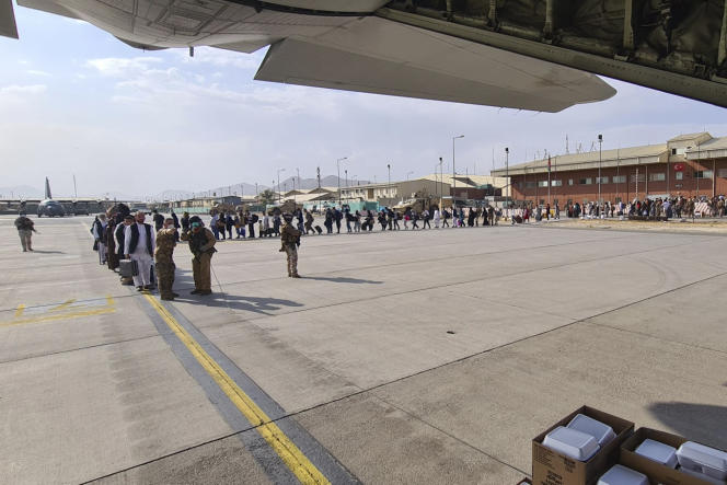 On Sunday, August 22, 2021, passengers wait at the airport in Kabul to board an Italian military plane en route to Rome.