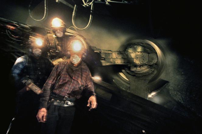 Des mineurs posent devant la haveuse de la mine de la Houve, à Creutzwald en Lorraine, le 2 avril 2004. Cette mine était la dernière exploitation de charbon en France, fermée définitivement en avril 2004.