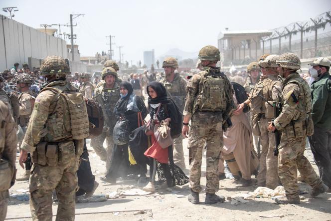 Des membres des armées britannique et américaine procèdent à l'évacuation des personnes d'Afghanistan, à l'aéroport de Kaboul, en août 2021.