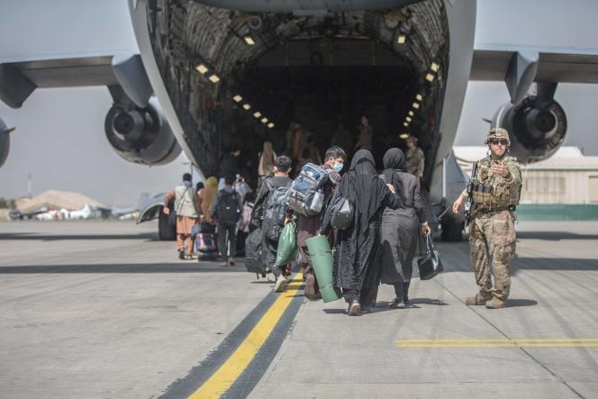 Des familles afghanes embarquent dans un avion de l'armée américaine afin d'être évacuées d'Afghanistan, à l'aéroport de Kaboul, en août 2021.