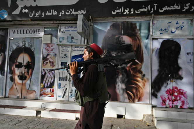 Dua siswa di depan salon kecantikan, poster yang menggambarkan wanita, pada 18 Agustus, di Kabul.