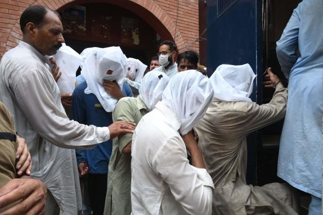 Des policiers escortent des hommes accusés d'avoir harcelé une femme dans un parc public de Lahore (Pakistan), le 21 août 2021.