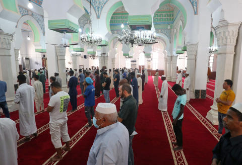 """A picture shows on August 11, 2021 Muslim men praying at the Sufi mosque in Tripoli's coastal city of Zliten, 150 kilometres east of the Libyan capital, which is alwo a zawiya -- an Arabic term for a Sufi institute offering religious education and free accommodation to travellers -- also includes boarding school and a university. - Despite Sufism's long history across North Africa, Libya's plunge into chaos after dictator Moamer Kadhafi was ousted in a 2011 revolt gave a free hand to militias. They included hardline Islamists, who are deeply hostile to Sufi """"heretics"""" and their mystical nighttime ceremonies aimed at coming closer to the divine. All the while, followers of the Muslim mystical tradition are working to renovate and preserve their heritage. (Photo by Mahmud TURKIA / AFP)"""