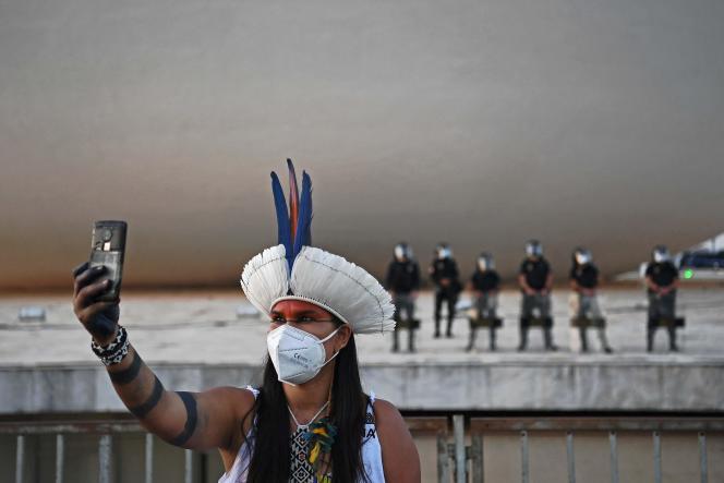 Une indigène prend un selfie devant la police antiémeute, lors d'une manifestation devant le bâtiment de la Cour suprême, à Brasilia, le 24août2021.