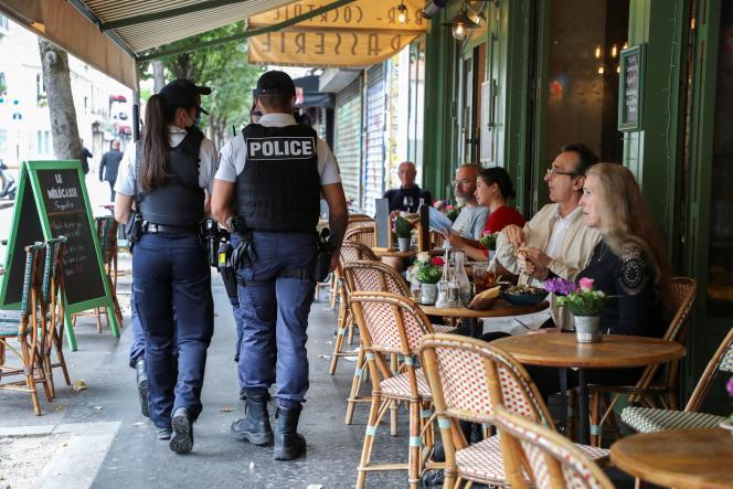 Des policiers patrouillent devant un restaurant parisien pour vérifier la conformité de l'application du passe sanitaire, le 18 août 2021.