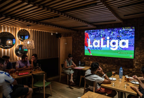 Soccer fans watch the La Liga match between FC Barcelona and Real Sociedad in a bar in Barcelona, Spain, on Sunday Aug. 15, 2021. Spains soccer clubs backed a proposal from CVC Capital Partners to pump $2.5 billion into the nations top soccer league that will leave FC Barcelona and Real Madrid, powerful opponents of the deal, on the margins. Photographer: Angel Garcia/Bloomberg via Getty Images