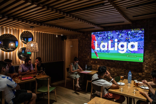 Des supporteurs regardent un match du championnat espagnol dans un bar, à Barcelone, le 15août 2021.