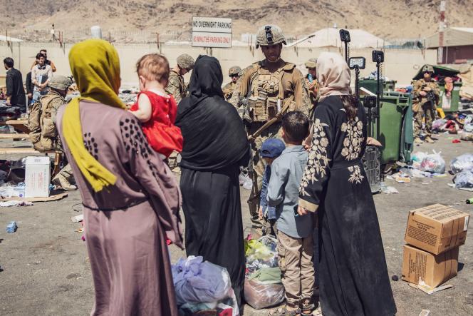 Des marines accueillent des Afghans qui attendent d'être évacués depuis l'aéroport militaire de Kaboul, samedi 28 août.