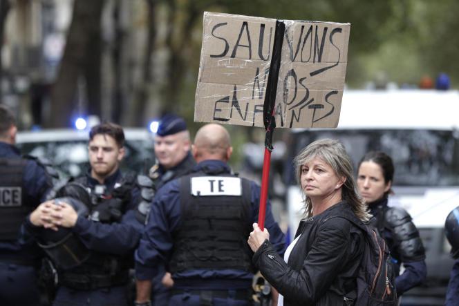 Une femme tient une pancarte «Sauvons nos enfants», lors d'une manifestation contre le passe sanitaire organisée à Paris, le 21août2021.