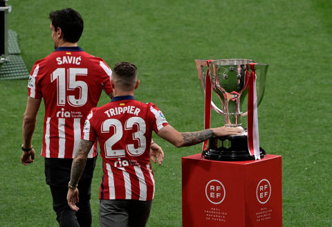 Atletico Madrid's Montenegrin defender Stefan Savic and Atletico Madrid's English defender Kieran Trippier walk past the trophy at the Wanda Metropolitano stadium in Madrid on May 23, 2021 after winning the Spanish Liga Championship title. - Atletico Madrid were crowned La Liga champions for the first time since 2014 at the end of a draining season shaped by the Covid-19 pandemic. (Photo by JAVIER SORIANO / AFP)