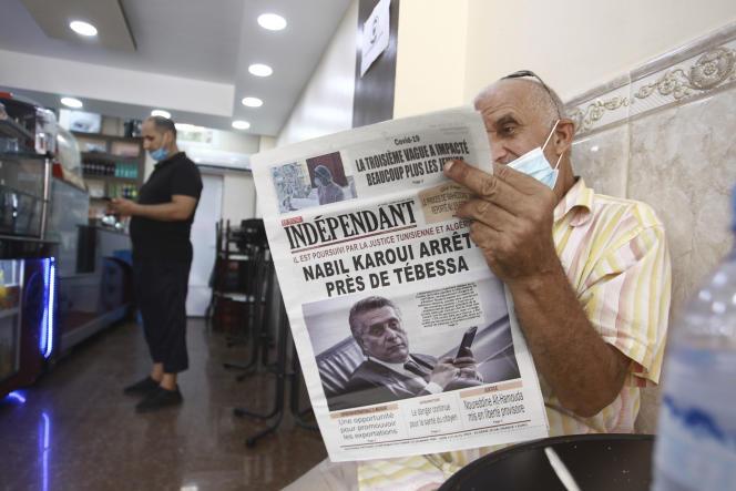 Sur la « une» du journal lu par un homme, à Alger, le 31 août 2021, la nouvelle de l'arrestation de Nabil Karoui, ancien candidat à la présidentielle tunisienne et magnat des médias, dans la région frontalière de Tebessa (Algérie).