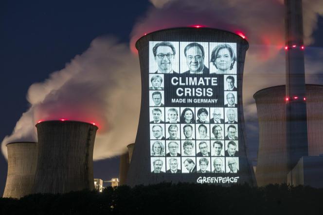 « Crise climatiquemade in Germany » : projection par Greenpeace de portraits de personnalités politiques allemandes sur une cheminéede la centrale thermique de Neurath (Rhénanie-du-Nord-Westphalie).