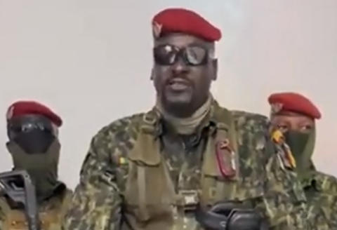 """A screengrab taken from footage sent to AFP by a military source on September 5, 2021 shows Guinean Colonel Doumbouya delivering a speech following the capture of the President of Guinea Conakry and the dissolution of the government during a coup d'etat in Conakry on September 5, 2021. Turmoil engulfed the impoverished west African nation of Guinea again on September 5, 2021 as army putschists said they had captured the president and staged a coup, and the government insisted it has repelled the attack. """"We have decided, after having taken the president, to dissolve the constitution,"""" said a uniformed officer flanked by soldiers toting assault rifles in a video sent to AFP. - RESTRICTED TO EDITORIAL USE - MANDATORY CREDIT """"AFP PHOTO / MILITARY SOURCE"""" - NO MARKETING - NO ADVERTISING CAMPAIGNS - DISTRIBUTED AS A SERVICE TO CLIENTS (Photo by MILITARY SOURCE / AFP) / RESTRICTED TO EDITORIAL USE - MANDATORY CREDIT """"AFP PHOTO / MILITARY SOURCE"""" - NO MARKETING - NO ADVERTISING CAMPAIGNS - DISTRIBUTED AS A SERVICE TO CLIENTS"""