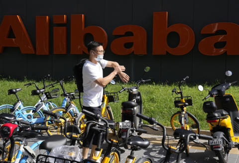 A man passes by the logo for Alibaba outside the Beijing headquarters in Beijing, China, Tuesday, Aug. 24, 2021. In a statement issued late Monday, Sept. 6, 2021, Chinese prosecutors have dropped a case against a former Alibaba manager accused of sexual assault by an employee, weeks after the case caused a backlash against the e-commerce firm for the improper handling of alleged sexual misconduct. (AP Photo/Ng Han Guan)
