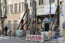 A man walks past fences set up around a collapsing buiding in central Marseille, southern France, on February 23, 2021. - Two years after the collapse of two buildings on the Aubagne street, which left eight people dead, the fight against unhealthy housing is progressing slowly in Marseille. (Photo by NICOLAS TUCAT / AFP)
