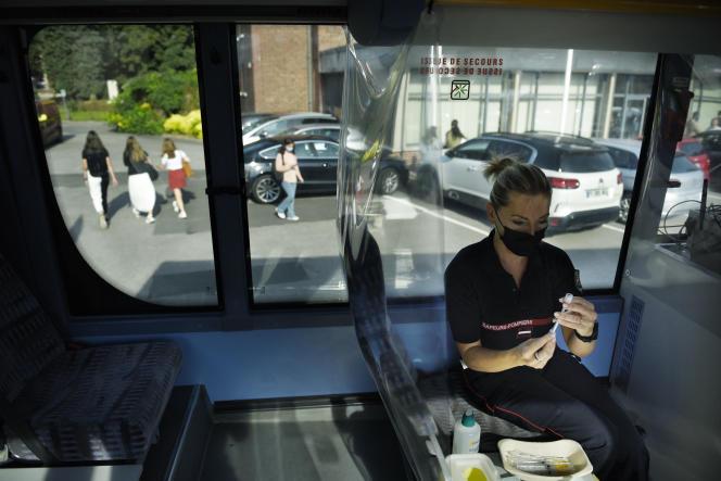 A l'intérieur du bus, un pompier prépare des doses de vaccins anti-Covid. A Amiens, le 6septembre 2021.