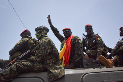 Lieutenant Colonel Mamady Doumbouya (C), head of the Army's special forces and coup leader, waves to the crowd as he arrives at the Palace of the People in Conakry on September 6, 2021, ahead of a meeting with the Ministers of the Ex-President of Guinea, Alpha Conde. - Lieutenant Colonel Mamady Doumbouya, the leader of the latest coup in Guinea, is a highly educated, combat-hardened soldier who once served in France's Foreign Legion. Doumbouya's special forces on September 5, 2021 seized Alpha Conde, the West African state's 83-year-old president, a former champion of democracy accused of taking the path of authoritarianism. (Photo by CELLOU BINANI / AFP)