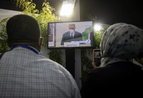 Journalists watch a television broadcast of Morocco's Minister of the Interior Abdelouafi Laftit announcing the results of the country's parliamentary and local elections in Rabat early on September 9, 2021. (Photo by FADEL SENNA / AFP)