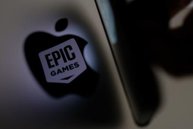 (FILES) In this file illustration photo taken on May 3, 2021, shows the Epic Games logo reflecting onto the Apple logo of the back of an I-mac in Los Angeles. A US judge ordered Apple on September 10, 2021 to change App Store practices in a long-awaited ruling in the antitrust case brought by Epic Games. The order said Apple can no longer oblige app developers to use its payment system, a hard-fought issue that could have far reaching implications. - (Photo by Chris DELMAS / AFP)