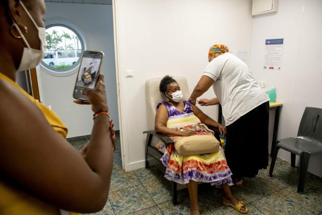 Des patients se font vacciner dans le centre de vaccination de l'aéroport de Pointe-à-Pitre le 7 septembre 2021. Ce centre, d'une capacité de plus 1000 patients par jour, est le plus grand de l'île.