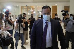 Alexandre Benalla, suivi par les journalistes dans les couloirs du tribunal, lors de son procès, à Paris le 13 septembre 2021.