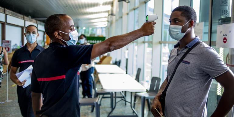 Un pompier contrôle la température à l'entrée du centre de vaccination de l'aéroport de Pointe-à-Pitre le 7 septembre 2021. Ce centre, d'une capacité de plus 1000 patients par jour, est le plus grand de l'île.  BRUNO FERT POUR LE MONDE.