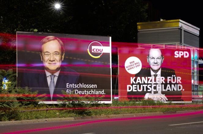 Poster oleh kandidat CDU-CSU Armin Laschet di sebelah kiri dan kandidat SPD Olaf Scholz di Berlin pada 13 September.