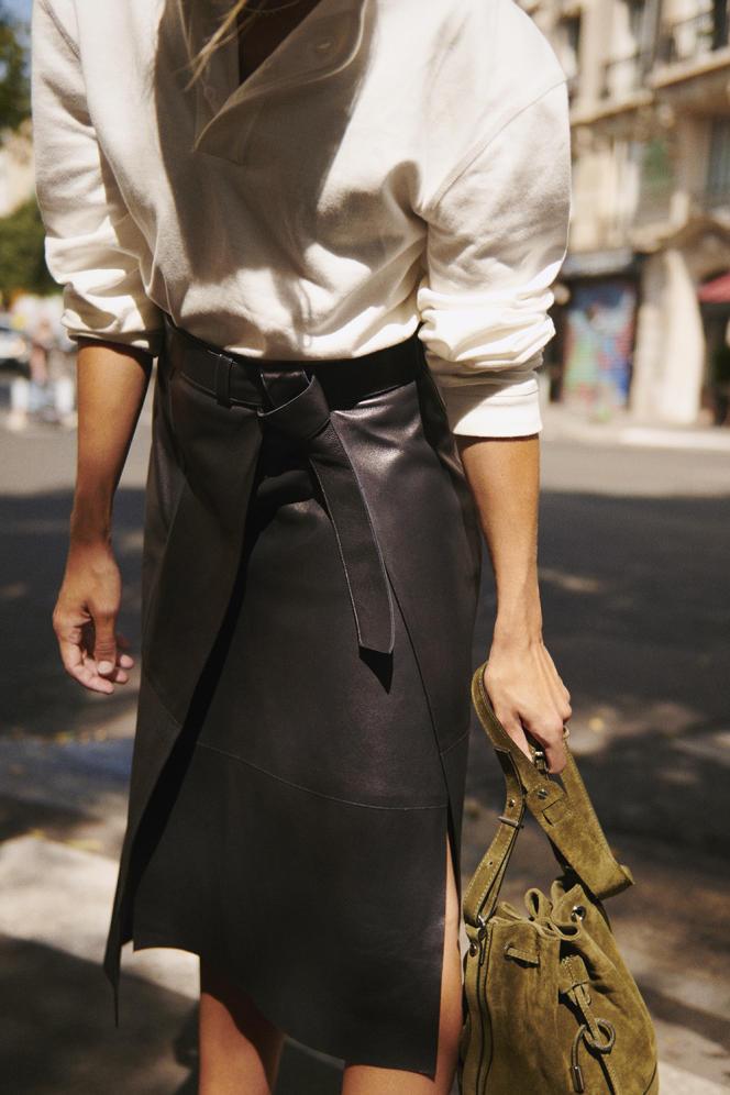 Tee-shirt col tunisien, en coton, Fursac, 95€. Jupe midi asymétrique, en cuir, Aeron, 995€. Sac Tina, en cuir suédé, The Kooples, 195€.