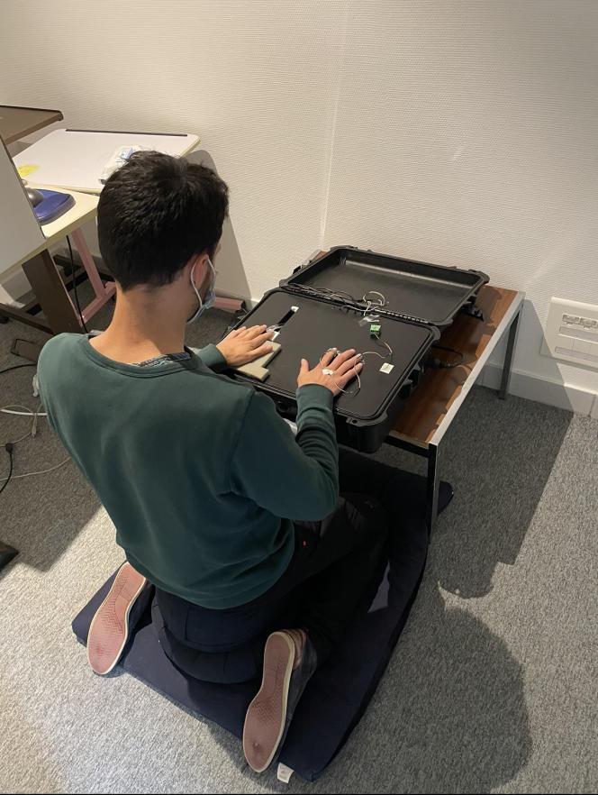 Un des membres de l'équipe de rechercheteste son dispositif d'évaluation de la perception tactile en posture de méditation.