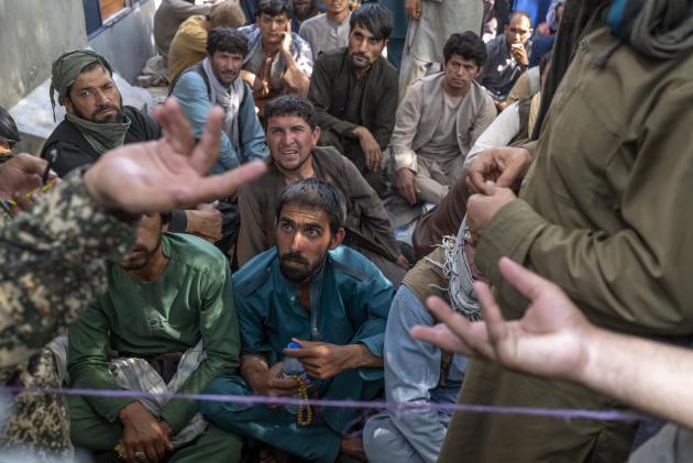 Des hommes attendent depuis le matin, certains depuis plusieurs jours, devant la New Kabul Bank, le 14 septembre 2021, à Kaboul.