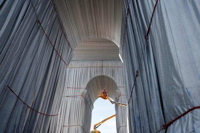 Des ouvriers enveloppent l'Arc de triomphe, pour une installation conçue par Christo et Jeanne-Claude, à Paris, le 16 septembre 2021.