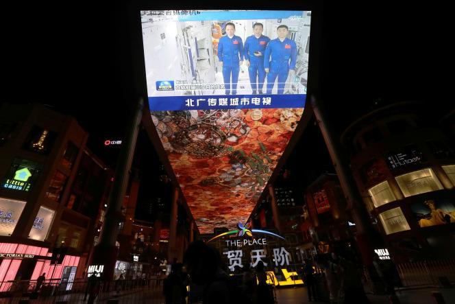 Sebuah layar raksasa menyiarkan kedatangan tiga astronot, yang disiarkan oleh saluran publik CCTV, di Beijing pada 16 September 2021.