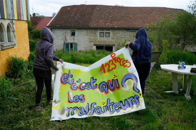 Deux militants s'apprêtent à accrocher une banderole sur la façade de la Maison de la résistance, àBure (Meuse), en mai 2020.