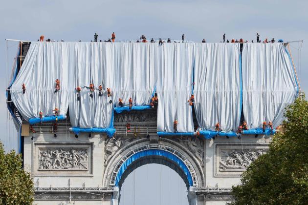 Le spectaculaire déploiement des lés de tissu par quelque 130 cordistes et charpentiers de Paris surl'Arc de triomphe, le 12 septembre 2021.