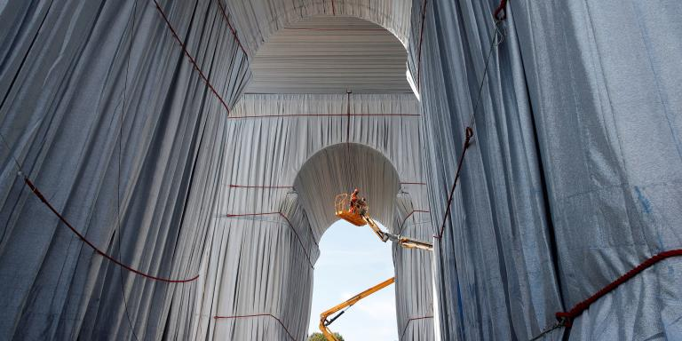 Workers install a shimmering wrapper to envelop the Arc de Triomphe monument, a posthumous installation known as
