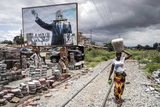 Une Guinéenne passe devant une affiche du président déchu Alpha Condé, à Conakry, le 16septembre 2021.