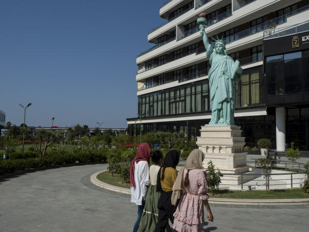 Afghan refugees walk past a replica of the Statue of Liberty at the resort that welcomes them in Shëngjin, Albania, September 15, 2021.