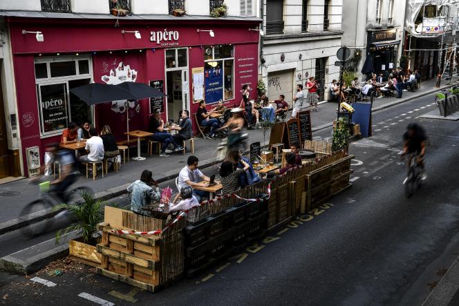 Des gens boivent un verre en terrasse d'un bar, quai de Jemmapes, dans le 10earrondissement parisien, le 23 juillet 2020.